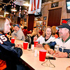 At far right, Beckley resident Darrell Bailey sports a Seahawks jersey while his wife, Bonnie Smith, wears a Saints jersey just prior to Super Bowl kickoff Sunday night at Calacino's. Their friend Jane Vass (left) was pulling for the Broncos while Bolt resident William Sabin (background middle left), wearing a Seahawks hat, was watching the team he's loved since 1979 when he was growing up in Seattle. Smith and Bailey aren't so much Seahawks and Saints fans as they are NFL fans in general. Every year, Smith buys a jersey for Bailey on his birthday and on Christmas. This year she bought Darrell a Cleveland Browns and Buffalo Bills jersey, and now, 16 years since she bought the first two, he has a jersey for every NFL team. <br /> Brad Davis/The Register-Herald