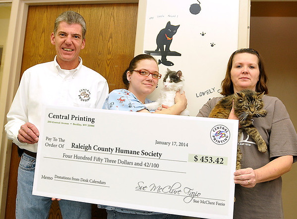 Scott Fazio, Vice President of Central Printing, presents a check to the Raleigh County Humane Society Friday afternoon at the animal shelter on Grey Flats Road. Accepting Central Printing's donation are shelter employees Nicole Shryock, middle, and Pam Romansic, along with shelter residents Delbert and Annabelle.<br /> Brad Davis/The Register-Herald