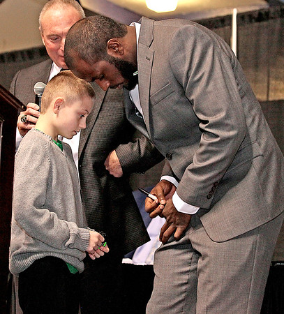 Marshall University quarterback Rakeem Cato signs an autograph for 9-year-old fan Braylon Arvon during the question and answer portion of the Big Atlantic Classic banquet Sunday afternoon at the Beckley-Raleigh County Convention Center. Though coach Doc Holliday and Cato were scheduled for an autograph session at the end of the banquet, Arvon decided not to wait, asking Cato if he'd sign a wristband he got from him during the Herd's Military Bowl win in Maryland. Without a second thought Cato agreed, and Arvon made his way onto the stage and got his wristband signed.<br /> Brad Davis/The Register-Herald