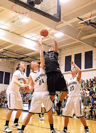 Wyoming East's John Morgan drives to the basket through a wall of Westside defenders Saturday night in Clear Fork.<br /> Brad Davis/The Register-Herald