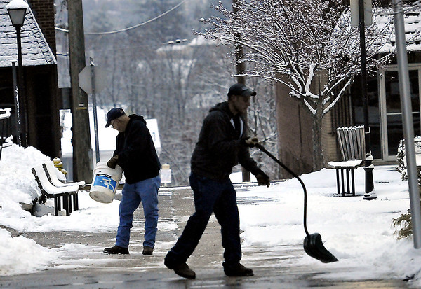 Raleigh County workers David Bell, left, and Roger Bowles, right, clear  paths before the Tuesday morning rush outside the Raleigh County Courthouse. F. Brian Ferguson/The Register-Herald