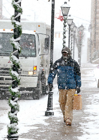 Downtown resident Naamon Carter carries home groceries as he walks through bitter cold and snow along Prince Street Monday afternoon. Temperatures dropped throughout the day yesterday and potential record lows are expected today.<br /> Brad Davis/The Register-Herald