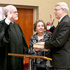 With his wife Lynn by his side, Bill O'Brien, right, is sworn in as mayor by judge Robert Burnside, Jr. Friday afternoon at city hall. O'Brien, best known as the former voice of the Woodrow Wilson Eagles after a 45-year career in broadcasting, takes over the remaining two years of former mayor Emmett Pugh's term, who recently resigned. That term will end June 30, 2016 when the next round municipal elections take place.<br /> Brad Davis/The Register-Herald