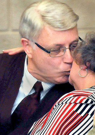 Bill O'Brien, left, receives a kiss from his wife Lynn, right, seconds after being voted in a the new Interim Mayor of Beckley during Thursday evening's Special Session of the Beckley Common Council. F. Brian Ferguson/The Register-Herald