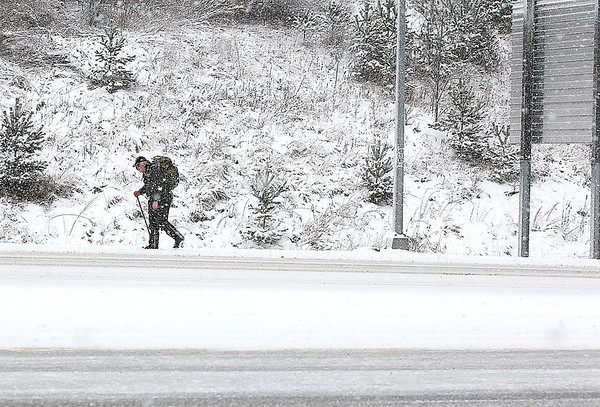 James Gryton Christian II, 59, hauls a backpack full of groceries as he trudges through the bitter cold and snow along Robert C. Byrd Drive between Crab Orchard and Sophia Monday afternoon. Christian, a Vietnam veteran who hasn't been able to drive since 2011 due to eye problems, makes a 5-mile hike from his home in Glen White to Crab Orchard three to four times a week anytime he needs to get groceries or handle any other errands. He was making his trip yesterday in anticipation of potential record low temperatures and more snow today that will have most area residents hunkered down trying to stay warm.<br /> Brad Davis/The Register-Herald