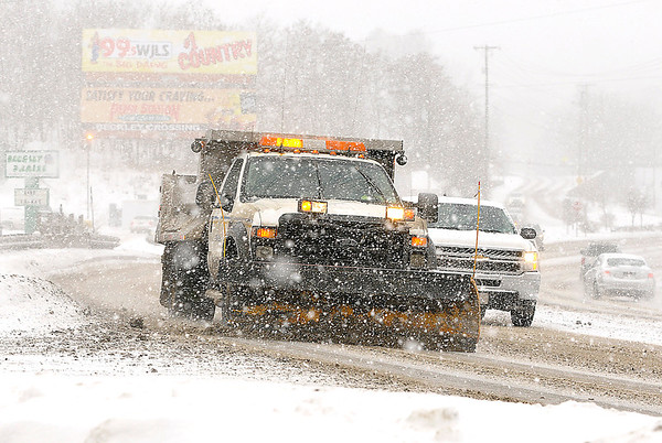A Division of Highways snow plow scrapes it's way along Robert C. Byrd drive Saturday afternoon as another Alberta clipper rolled through the state, again making roads treacherous and keeping crews out at all hours of the day trying to keep highways clear.<br /> Brad Davis/The Register-Herald