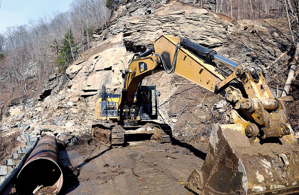 An excavator works on Rt.3, in Sundial, as crews continue attempting to clear the rockslide that has cut off the road that connects Raleigh and Boone Counties. F. Brian Ferguson/The Register-Herald