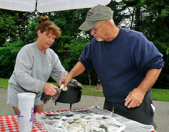 Phillip Weaver places freshly cut biscuit dough into a hot frying pan as his wife Becky holds it for him early Sunday morning at the Lake Stephens RV campground. The former Lincolnton, North Carolina residents spend virtually every weekend camping at Lake Stephens, and they've quickly developed a tradition of making one of the best homemade, open fire-cooked breakfasts around. They now live in the Morgan Hills area, and word of the Weavers' awesome biscuits is beginning to spread outside the campground thanks to camping neighbors lucky enough to get a shot at whatever's left over.<br /> Brad Davis/The Register-Herald