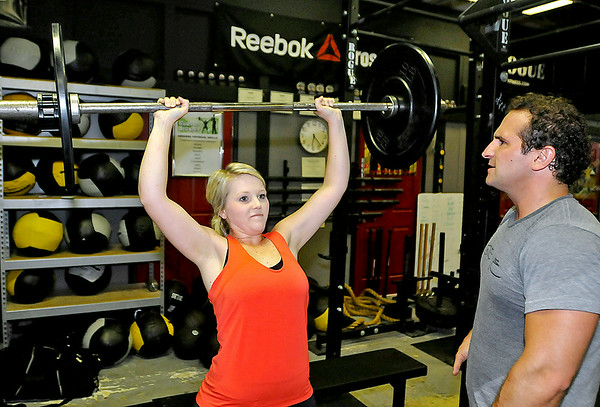 Kelly Taylor lifts weights as fellow athlete Chip Williams, right, keeps count of her reps during a CrossFit session July 15 at L.A. East Fitness on Mountaineer Drive.<br /> Brad Davis/The Register-Herald