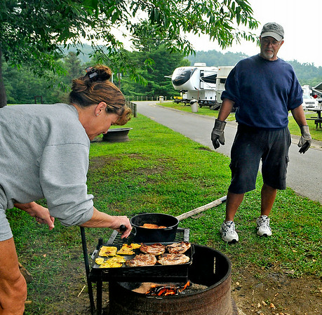 Phillip watches the biscuits closely as his wife Becky handles the pork chops and eggs, which she was in charge of early Sunday morning at the Lake Stephens RV campground. Cooking on a open fire is a bit of a different world, as you can't just turn the heat down if you're over cooking something. The Weavers' biscuits have the perfect mix of crunchy outside and chewy inside thanks largely to perfect timing.<br /> Brad Davis/The Register-Herald