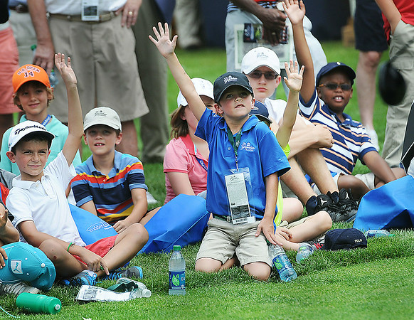 Youths raise their hands in hopes of being a volunteer in the youth Day Clinic on Tuesday at the Greenbrier Classic in White Sulpher Springs. F. Brian Ferguson/The Register-Herald