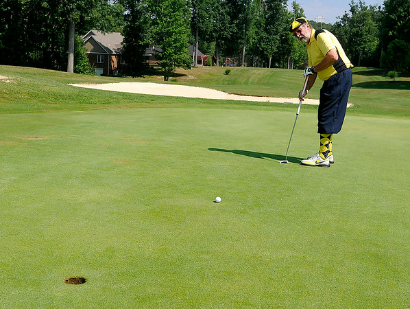 Mullens resident Roy Forren, who wasn't trying to pull off the perfect Payne Stewart impression with his WVU colors, putts at the Brier Patch Golf Course Saturday morning during the 34th annual BNI tournament.<br /> Brad Davis/The Register-Herald