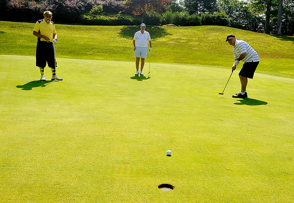 Mullens resident Roy Forren, left, and Gastonia, North Carolina resident Greg Simmons, middle, watch as Clover, South Carolina resident Mark Hall nearly sinks a birdie putt on the 11th hole at the Brier Patch Golf Course Saturday morning during the 34th annual BNI tournament.<br /> Brad Davis/The Register-Herald