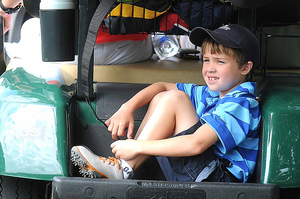 Cooper Childress, 7, son of Nicole Childress, sits in the back of a golf cart watching the BNI Golf Tournament on the Cobb course at Glade Springs.<br /> Rick Barbero/The Register-Herald