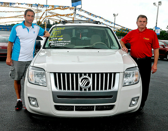 Jay Rist (left), CEO of the YMCA of Southern West Virginia, and Keith Tyler, General Manager of Mountaineer Automotive, pose for a quick photo with a 2009 Mercury Mariner that will be given away as a prize at the Friends of Coal Auto Fair this weekend. The pre-owned vehicle has 87,000 miles and people can enter to win it, free of charge, by filling out entry cards during the fair, which begins Thursday and runs through Sunday at the Paul Cline Memorial Sports (YMCA Soccer) Complex. The winner will be drawn Saturday.<br /> Brad Davis/The Register-Herald