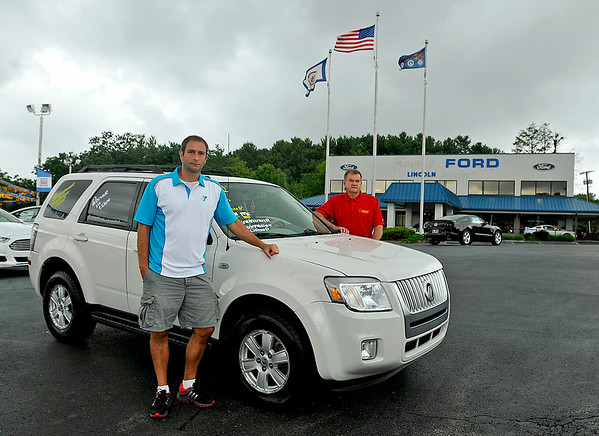 Jay Rist (near), CEO of the YMCA of Southern West Virginia, and Keith Tyler, General Manager of Mountaineer Automotive, pose for a quick photo with a 2009 Mercury Mariner that will be given away as a prize at the Friends of Coal Auto Fair this weekend. The pre-owned vehicle has 87,000 miles and people can enter to win it, free of charge, by filling out entry cards during the fair, which begins Thursday and runs through Sunday at the Paul Cline Memorial Sports (YMCA Soccer) Complex. The winner will be drawn Saturday.<br /> Brad Davis/The Register-Herald