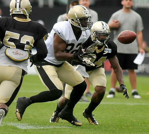 Tight end Benjamin Watson, middle, tries to catch a pass as defensive back Corey White, right, reaches in to break it up during Saints training camp July 27 in White Sulphur Springs.<br /> Brad Davis/The Register-Herald