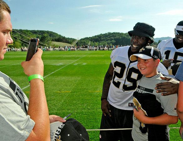 Charlotte, North Carolina resident Justin Sabido poses with running back Khiry Robinson as his brother Cameron, far left, snaps a photo after practice Saturday afternoon in White Sulphur Springs.