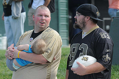 Robert May holding his son Blake May, 9 months, of Lewisburg, left, and Zach Arms, of Abingdon, Va. take in the New Orlean's Saints first day of training camp on the new practice fields at The Greenbrier Resort. Rick Barbero/The Register-Herald