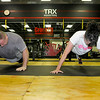 Thomas Stalnaker, left, and Sherri Thomas grind through a series of pushups during a CrossFit session at L.A. East Fitness on Appalachian Drive July 15.<br /> Brad Davis/The Register-Herald