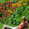 A fan relaxes in the sun by a flower garden between holes 8 and 9 during the Greenbrier Classic Friday in White Sulphur Springs.<br /> Brad Davis/The Register-Herald