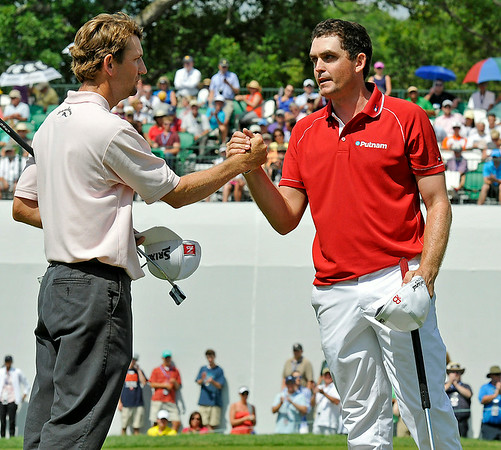 George McNeill, left, and pairing partner Keegan Bradley shake hands on the 18 green following their final round of the Greenbrier Classic Sunday in White Sulphur Springs.<br /> Brad Davis/The Register-Herald
