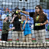 """11-year-old Billy Smith, middle, winds up to fire a tennis ball while his opponent, 10-year old Andrew Lovell, reaches for another ball from Miner's Minion Jenna Plummer (right) Tuesday night at Linda K. Epling Stadium. The two Beckley residents got the chance to participate in the West Virginia Miners' Window World Windup contest between the second and third innings, where the object is to place as many throws through the """"window"""" as possible. Neither was able to score a direct hit, but the both came away winners after getting to spend a few moments on the field in front of the crowd.<br /> Brad Davis/The Register-Herald"""