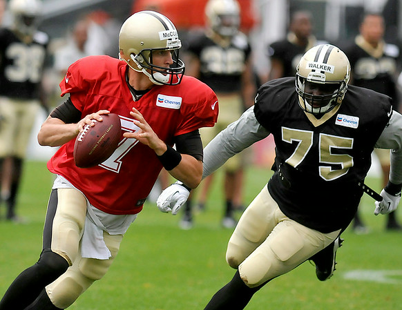 Backup quarterback Luke McCown is flushed from the pocket as he is pursued by defensive lineman Tyrunn Walker during Saints training camp July 27 in White Sulphur Springs.<br /> Brad Davis/The Register-Herald