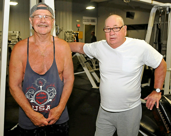 Beckley residents Tom Rapp, left, and Bill Sweeny take a quick break from their workout to pose for a quick photo Monday morning at L.A. East Fitness on Appalachian Drive. The two 77-year-olds have been life-long friends since they were six, and often work out together at the gym. Rapp makes it out four times a week while Sweeny exercises at the gym at least three times per week, mixing in other days working out at home.<br /> Brad Davis/The Register-Herald