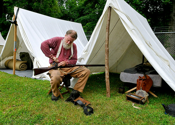 Princeton resident and Confederate infantryman Jim Wood cleans his rifle outside of his encampment following the re-enactment of a Civil War battle Sunday afternoon at the Oceana Middle School football field. The North and South fought again as re-enactors depicted the skirmish at Methany Chapel, the only Civil War action seen in Wyoming County.<br /> Brad Davis/The Register-Herald