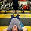 Webster resident Thomas Stalnaker battles through a series of situps as fellow athlete Jonathan Froble pushes him to finish the workout during a CrossFit session July 15 at L.A. East Fitness on Mountaineer Drive.<br /> Brad Davis/The Register-Herald