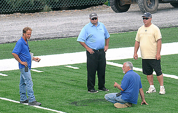 Kelly Shumate, center, speaks with the grounds crew on the New Orleans practice field at The Greenbrier Resort.<br /> Rick Barbero/The Register-Herald