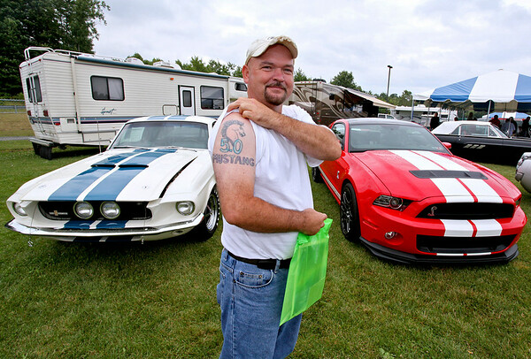 Madison resident Billy Brown shows off his tattoo as he poses with a pair of Shelby Mustangs during the 11th Annual Friends of Coal Auto Fair Saturday afternoon the YMCA Paul Cline Memorial Youth Sports Complex. Brown doesn't own these Shelbys, but he describes himself as one of the biggest Mustang fans in the world ever since his first ride in a 1966 Fastback 289 Hi-Po way back in the day.<br /> Brad Davis/The Register-Herald