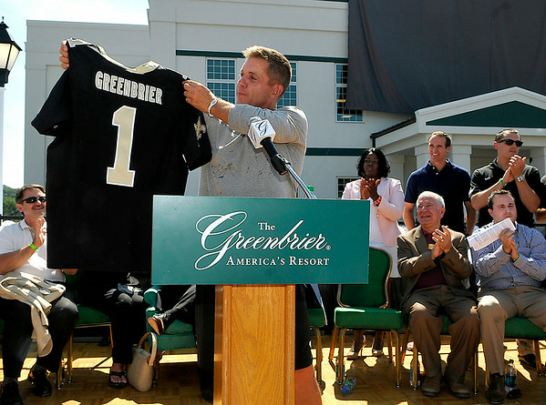 New Orleans Saints head coach Sean Payton shows off a Greenbrier jersey he presented as a gift to the resort during a grand opening ceremony for the brand new practice facility, dubbed the Advocare Sports Performance Center, Saturday afternoon in White Sulphur Springs. Resort owner Jim Justice also received his own Saints jersey. <br /> Brad Davis/The Register-Herald