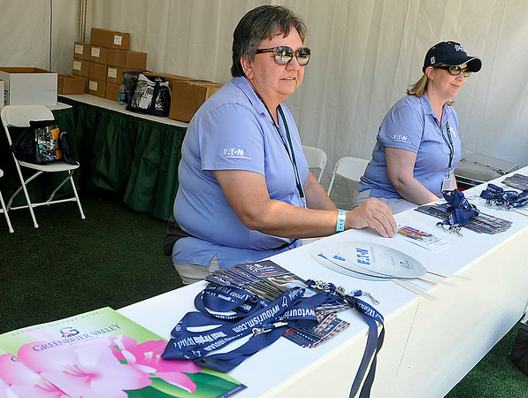 Kitty Morton, left, and Mary Ann Bonadeo work the information desk at the Greenbrier Classic Saturday afternoon in White Sulphur Springs. Tee times, course maps, player pairings and the answers to any questions fans and visitors might have can be found at their tent, located outside of Founder's Park in the middle of the Old White course area.<br /> Brad Davis/The Register-Herald