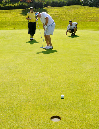 Mullens resident Roy Forren, left, and Clover, South Carolina resident Mark Hall, right, watch as Gastonia, North Carolina resident Greg Simmons, middle, nearly sinks a putt on the 11th hole at the Brier Patch Golf Course Saturday morning during the 34th annual BNI tournament.<br /> Brad Davis/The Register-Herald