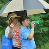 Mayra Parker, left, and son Joshua Parker, right, both of Monroe County, battle steamy temperatures as they try to stay cool during the youth Day Clinic on Tuesday at the Greenbrier Classic in White Sulpher Springs. F. Brian Ferguson/The Register-Herald