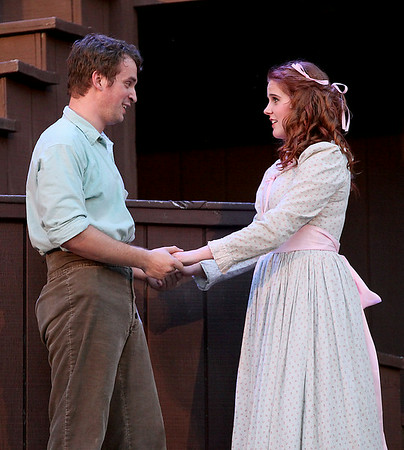 Benjamin Stoll, playing Johnse Hatfield, and Allie Patton, playing Roseanne McCoy, perform during Theatre West Virginia's Hatfields & McCoys Friday night at Grandview Park's Cliffside Amphitheatre.<br /> Brad Davis/The Register-Herald