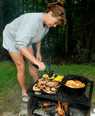 Phillip's wife Becky prepares the rest of the breakfast, eggs and pork chops, along with the biscuits over an open fire Sunday morning at the Lake Stephens RV campground. <br /> Brad Davis/The Register-Herald
