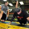 Chip Williams, left, pushes fellow athlete Tommy McClung as he keeps count of his pushups during a CrossFit session July 15 at L.A. East Fitness on Mountaineer Drive.<br /> Brad Davis/The Register-Herald