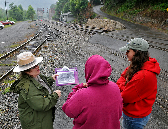 Jodi French-Burr (left), with the National Park Service, shows Toms River, New Jersey residents Jessica Schreuder, middle, and Nichole Letizia a photo of what the downtown area looked like many years ago from where they're standing Saturday morning in Thurmond. The two AmeriCorps volunteers stopped by the old Fayette county boomtown for its first Railroad Day, an event celebrating the rich history of the town and the significance of the railroad's influence upon it.<br /> Brad Davis/The Register-Herald