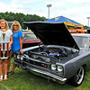 Lester resident Jay Matics, far left, joins his wife Theresa, right, and his daughter Nyah for a quick photo Sunday afternoon during the closing moments of the Friends of Coal Autofair at the YMCA Paul Cline Memorial Youth Sports Complex. His 1969 Dodge Coronet with a 665 horsepower-producing, 572 cubic inch Hemi engine earned him Participants Pick Best of Show, the fair's top prize. The award was based on participant voting, and his ride will represent next year's auto fair in all promotional materials.<br /> Brad Davis/The Register-Herald