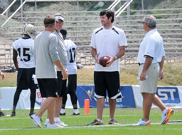 Bubby Watson, center holding football, speaks with some of the New Orlean's Saints coaching staff  during the first day of training camp on the new practice fields at The Greenbrier Resort.<br /> Rick Barbero/The Register-Herald