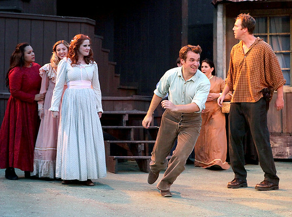 Johnse Hatfield, played by Benjamin Stoll, scampers off after charming Roseanne McCoy (3rd from left), played by Allie Patton, as her brother Tolbert (far right), played by Jason Adkins, glares at her in anger during Theatre West Virginia's Hatfields & McCoys Friday night at Grandview Park's Cliffside Amphitheatre.<br /> Brad Davis/The Register-Herald