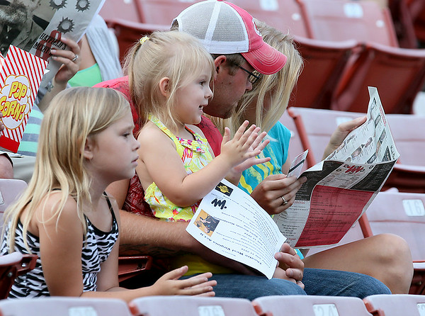 Three-year-old Ally Day, 2nd from left, applauds as Sacred Heart Ministries finishes up their pre-show performance prior to the start of Theatre West Virginia's Hatfields & McCoys Friday night at Grandview Park's Cliffside Amphitheatre. Her 7-year-old sister Trinity at left can't wait for the show to start while her mom and dad, Charles and Kristen check out the program.<br /> Brad Davis/The Register-Herald