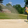 Mullens resident Roy Forren, who wasn't trying to pull the perfect Payne Stewart impression with his WVU colors, chips from a bunker at the Brier Patch Golf Course Saturday morning during the 34th annual BNI tournament.<br /> Brad Davis/The Register-Herald