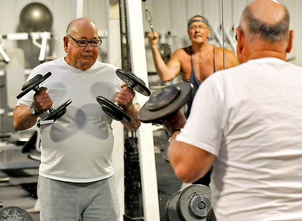 77-year-old Beckley resident Bill Sweeny, left, does dumbbell curls while his life-long buddy Tom Rapp watches in the background at right Monday morning at L.A. East Fitness. The ageless Sweeny works out at the Appalachian Drive location three times a week and also exercises at home regularly.<br /> Brad Davis/The Register-Herald