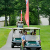Amateur golfers John Brophy (lower right, driving) and David Carney drive their golf cart to the next hole with a bit of extra decoration, one of the West Virginia Golf Association flags that can be found around the Cobb golf course at Glade Springs Resort Monday afternoon during the West Virginia Open Pro-Am. Their pro, five time Open winner Brad Westfall, can be seen getting a laugh out of it in the following cart, while the other two amateurs in the group, Ray Chapman (back left) and Johnny Hutchins follow suit with a flag of their own.<br /> Brad Davis/The Register-Herald