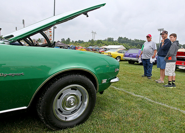 Classic car enthusiasts and Lewisburg residents Jim Moore (middle) and his son Cameron, 13, chat with Peterstown resident Alvin Maxey about his 1968 Chevy Camaro Z28 Rally Sport during the 11th Annual Friends of Coal Auto Fair Saturday afternoon the YMCA Paul Cline Memorial Youth Sports Complex. The Moores own a 1957 Chevrolet of their own, and young Cameron says he absolutely loves Camaros.<br /> Brad Davis/The Register-Herald
