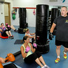 Kickboxing instructor Dave Krass instructs his class as they drop down for sit-ups during a session June 10 at the YMCA of Southern West Virginia.<br /> Brad Davis/The Register-Herald